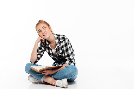 Smiling pensive ginger woman in shirt sitting on the floor with book and looking up over white background