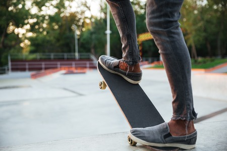 Young african man doing skateboarding outdoor in a skate park