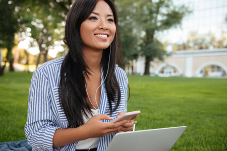 Close-up portrait of young cheerful asian woman, holding laptop, while listening to music, looking aside, outdoor