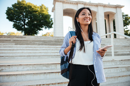 bajando escaleras: Happy young asian woman in striped shirt and earphones, listening to music, while going down stairs