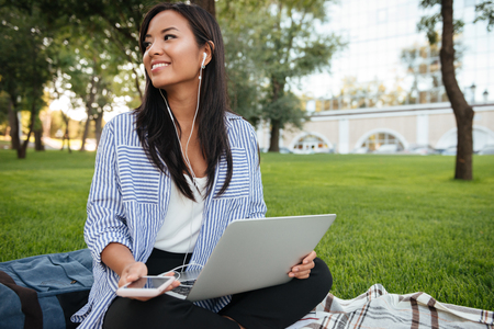 Retrato de joven mujer asiática alegre, sosteniendo la computadora portátil, mientras escucha música, mirando a un lado, al aire libre Foto de archivo