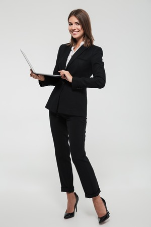 Full length portrait of a confident smiling businesswoman in suit holding laptop computer and looking at camera isolated over white background Archivio Fotografico