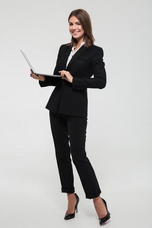 Volledig lengteportret van een zekere glimlachende onderneemster in laptop van de kostuumholding computer en het bekijken camera die over witte achtergrond wordt geïsoleerd
