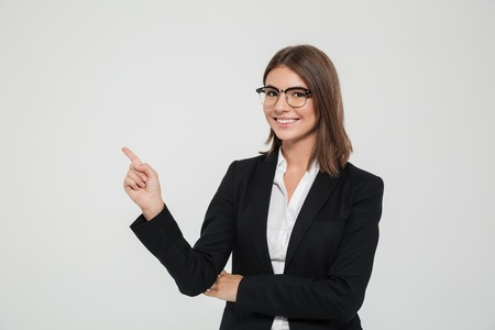 Portrait of a good tempered young businesswoman in suit pointing finger away at copy space isolated over white background