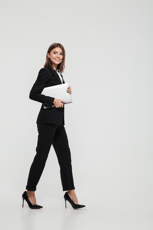Full length portrait of a confident pretty businesswoman in suit holding laptop computer while walking and looking at camera isolated over white background