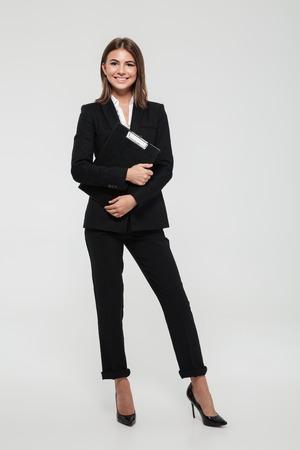 Ganzaufnahme einer glücklichen lächelnden Geschäftsfrau in der Klage, die Klemmbrett hält und die Kamera lokalisiert über weißem Hintergrund betrachtet Standard-Bild