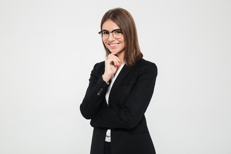 Portrait of smiling brown-haired businesswoman in suit and eyeglasses standing with arm on her chin and looking at camera isolated over white background