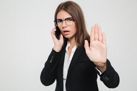Portrait of a serious busy businesswoman in eyeglasses and suit showing stop gesture with her plam while talking on mobile phone isolated over white background