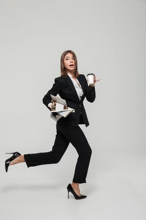 Het portret van een grappige bezige onderneemster in kostuumholding haalt koffiekop en een krant weg terwijl laat het lopen en bekijkend camera die over witte achtergrond wordt geïsoleerd Stockfoto - 89362125