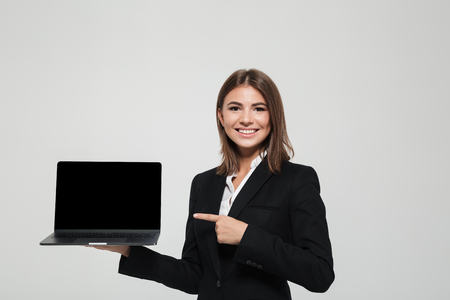 Portrait of a smiling businesswoman in suit pointing finger at blank screen laptop computer while standing and looking at camera isolated over white background