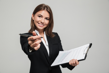 Portrait of an attractive friendly businesswoman in suit holding documents while standing and giving you a pen isolated over white background Stock Photo