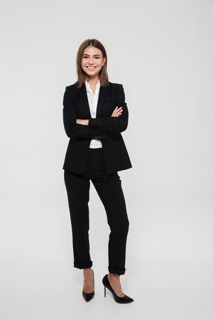 Ganzaufnahme der glücklichen netten Geschäftsfrau in der Klage, die mit den Armen steht, faltete sich und die Kamera betrachtend, die über weißem Hintergrund lokalisiert wurde