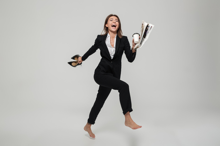 Full length portrait of cheery satisfied businesswoman holding high heel shoes and newspaper while running isolated over white background Reklamní fotografie