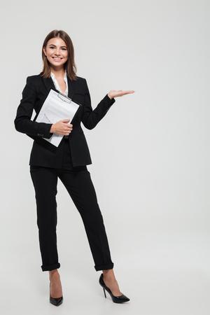 Retrato de cuerpo entero de una empresaria joven alegre en traje sosteniendo portapapeles con documentos y sosteniendo espacio de copia en su palma aislada sobre fondo blanco