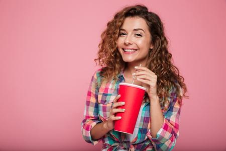 カジュアルなコーラを飲むとピンクの上分離ポーズかなり白人女性を笑顔