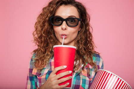 Portrait of serious lady in 3d glasses drinking cola and holding popcorn isolated