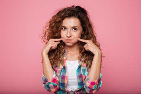 ピンクの上分離したしかめっ面のカジュアルな服での面白いかなりの女性の肖像画 写真素材