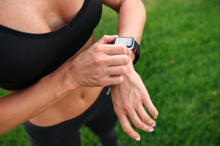 Cropped image of strong young sports woman outdoors using watch.