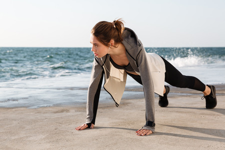 Photo of young healthy slim woman in sport wear standing in a plank position at the seaside