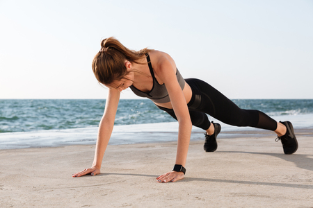 Photo of young female athlete standing in a plank position at the seaside