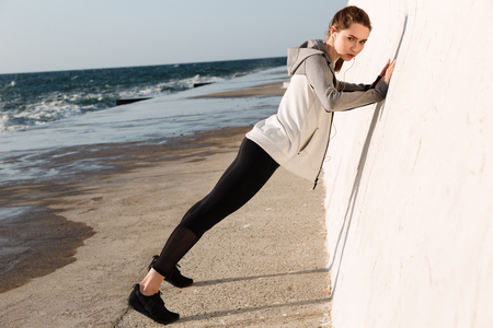 Full-length photo of  fit girl doing push-ups while standing near white wall, looking at camera, seaside outdoor