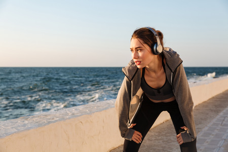 Portrait of charming caucasian runner woman listening to music while resting after workout