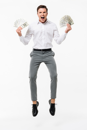 Full length portrait of a happy successful man in white shirt holding bunch of money banknotes while jumping and looking at camera isolated over white background