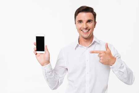 Portrait of a glad excited man in a white shirt pointing finger at blank screen mobile phone and looking at camera isolated over white background