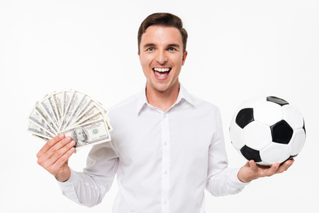 Portrait of a cheerful happy man in white shirt holding bunch of money banknotes and a soccer ball isolated over white background Stock Photo