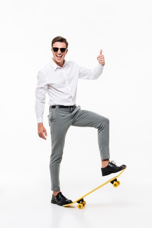 Full length portrait of a handsome successful man in white shirt and sunglasses posing with a skateboard and showing thumbs up gesture while standing and looking at camera isolated over white background Reklamní fotografie