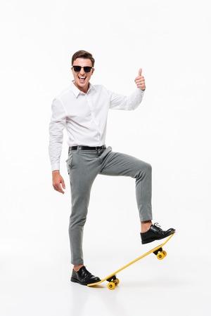 Het volledige lengteportret van een knappe succesvolle mens in wit overhemd en zonnebril die met een skateboard stellen en beduimelt omhoog gebaar tonen terwijl status en bekijkend camera geïsoleerd over witte achtergrond
