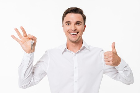 Portrait of a happy cheery man in white shirt holding keys and showing thumbs up gesture while looking at camera isolated over white background