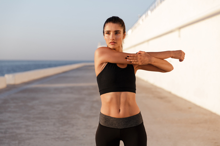 Young concentrated healthy woman stretching hands and training near sea