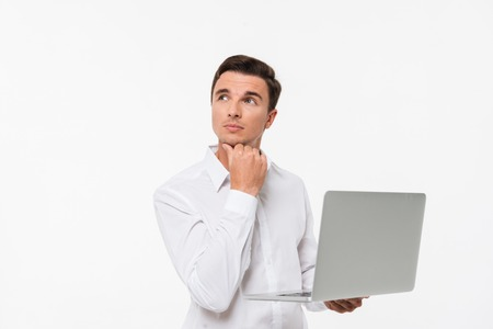 Portrait of a pensive thoughtful man in white shirt holding laptop computer while standing and looking away isolated over white background Stock Photo