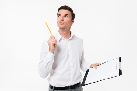 Portrait of a pensive handsome guy in white shirt and eyeglasses holding blank clipboard and looking away isolated over white background