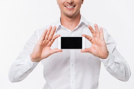 Close up portrait of a smiling man in a white shirt showing blank screen mobile phone with two hands and looking at camera isolated over white background Stock Photo