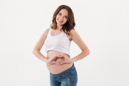 Image of pretty smiling pregnant woman standing isolated over white background. Looking camera showing heart love gesture.