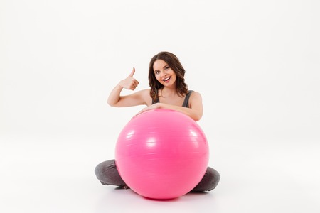 fitball: Happy pregnant woman sitting on the floor with fitball and showing thumb up while looking at the camera over white background Stock Photo
