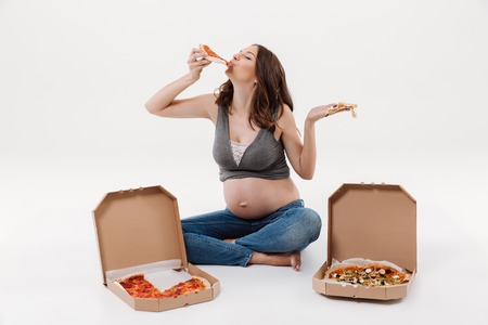 Image of amazing hungry pregnant woman isolated over white background. Looking aside eating pizza.