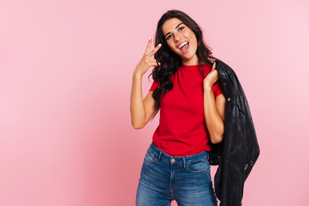 Happy brunette woman showing peace sign and looking at the camera while holding jacket on her shoulder over pink background Stock Photo
