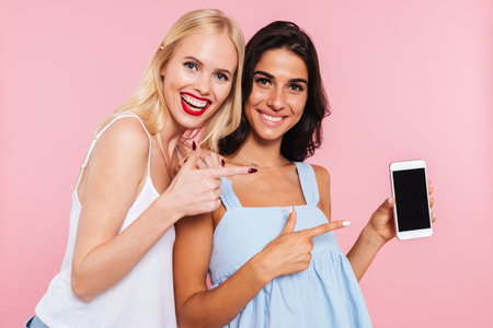 Portrait of cheerful caucasian ladies wearing casual showing blank screen of smartphone isolated