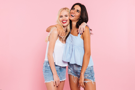 Cheerful female blonde and brunette friends hugging and laughing to camera isolated over pink Stock Photo