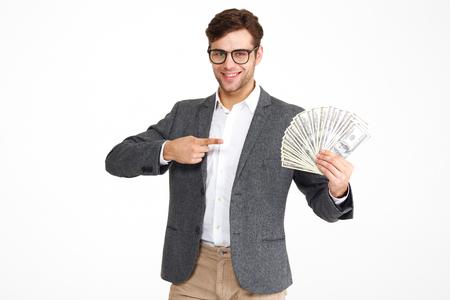 眼鏡の満足した若い男性の肖像画とお金の紙幣を持った上着立っている間に、白い背景の上に孤立して指を指して