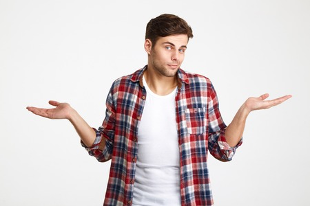 Portrait of a young doubtful man shrugging shoulders and looking at camera isolated over white background