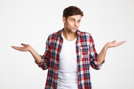 Portret van een jonge twijfelachtige mens die schouders ophaalt en camera bekijkt die over witte achtergrond wordt geïsoleerd