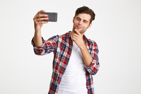 Portrait of a satisfied charming man taking a selfie while standing isolated over white background Stock Photo