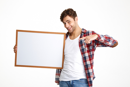 Portrait of a smiling casual guy pointing finger at blank board and looking at camera isolated over white background