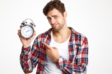 Portrait of a unsatisfied young man pointing finger at an alarm clock isolated over white background