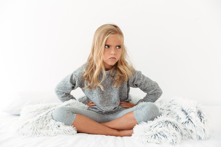 Photo of angry little girl with hands on her waist sitting with crossed legs in bed, looking aside Stock Photo