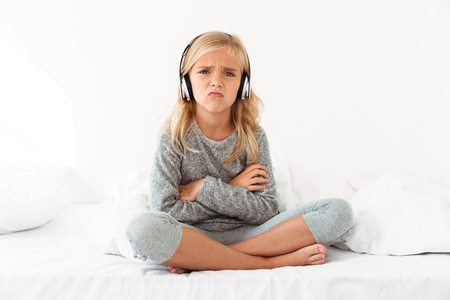 Upset female kid in headphones sitting with crossed arms and legs in bed, looking at camera Stock fotó